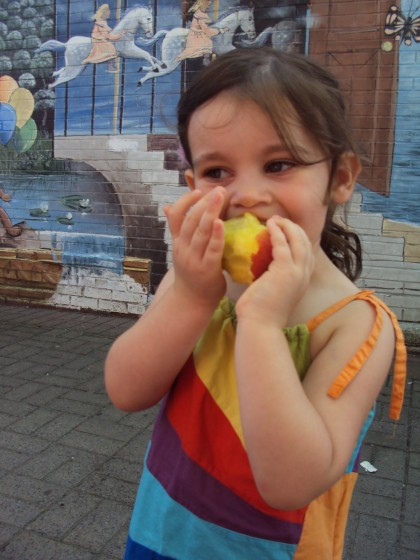 Lilly taste testing the peaches.